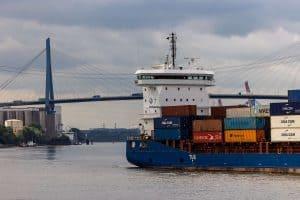 Containerschiff fährt unter der Köhlbrandbrücke hindurch, ein Pfeiler der Brücke erkennbar