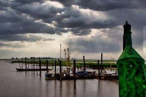 Blick über den Hafen in Petkum. Rechts eine alte Boje, einige Boote liegen im Hafen