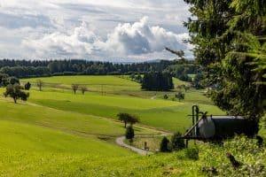 Blick ins Tal, rechts ein Wasserwagen, durch Bild schlängelt sich eine Straße. Im Hintergrund Wald. Dramatische Wolken.