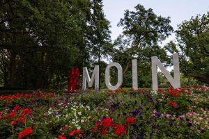 Im Vordergrund Blumen das Wort #MOIN in großen Buchstaben in der Bildmitte. Bäume im Hintergrund