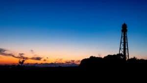 Der Leuchtturm Campen am rechten Bildrand. Am Fuße des Turmes Bäume. Links der Sonnenuntergang.