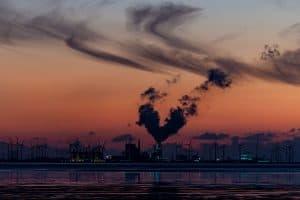 Industrie mit Windrädern im Abendlicht. Schleierwolken und der Schornstein der Fabrik entlässt einen fast herzförmigen Rauch