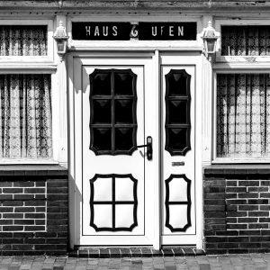 """Eine Haustür. Rechts und links noch Fenster. Über der Haustür der Schriftzug """"Haus Ufen"""" mit der Hausnummer 6"""