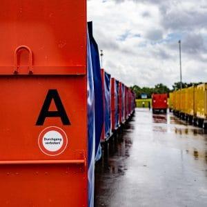 """Der Buchstabe A am rechten Bildrand, darunter der Schriftzug """"Durchgang verboten"""". Transportwagen verschoben zum Bildhintergrund und am rechten Rand"""