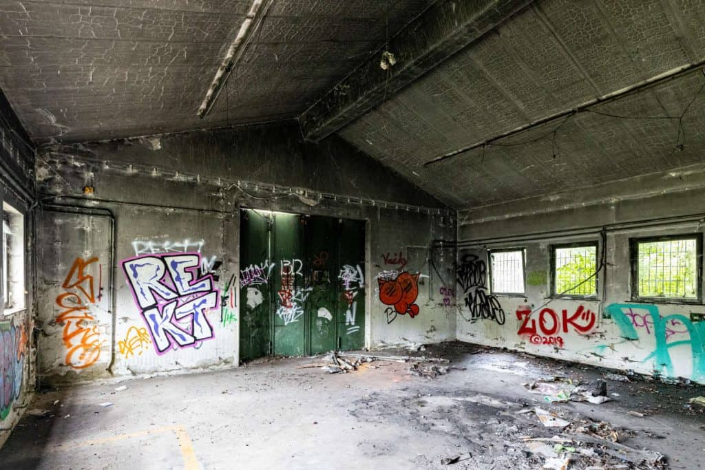 Eine größere Halle, rechts Fenster, im Hintergrund das Hallentor, an den Wänden Graffitis