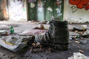 Ein einzelner Schuh, um den Schuh herum Müll