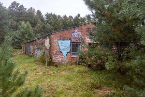 Altes Lagerhaus mit Graffiti, umringt von Bäumen.