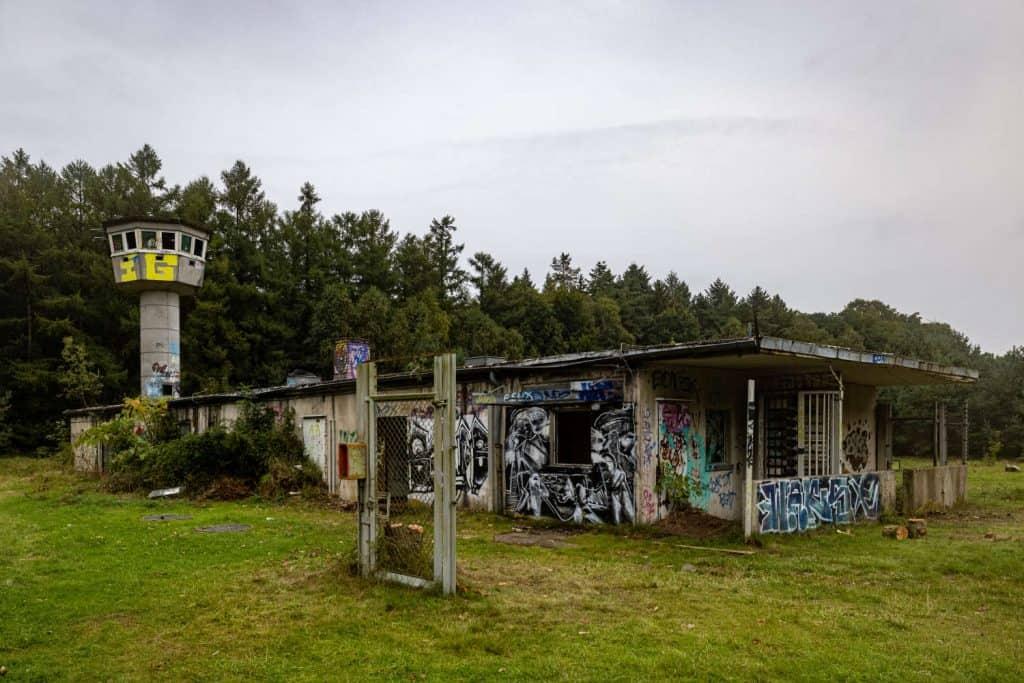 Baracke mit Wachturm im Hintergrund, vorne eine einzelne Eisenpforte