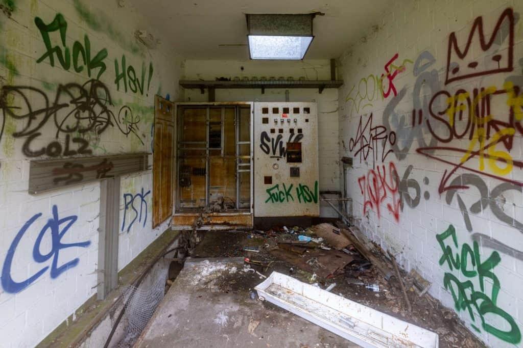 Blicke in einen Raum mit einem alten Schaltschrank an der Wand, Graffiti