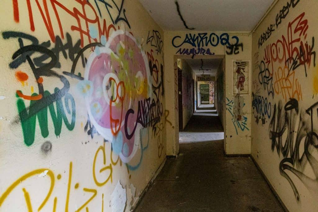 Blick über einen Flur durch mehrere Türen. An den Wänden Graffitis