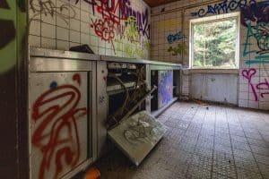 Edelstahlküche an der linken Seite des Raumes, rechts hinten ein Fenster, an den Wänden Graffiti
