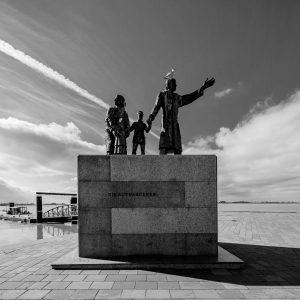 Auswandererdenkmal in Bremerhaven: Ein Granitblock mit der Aufschrift Die Auswanderer. Auf dem Block eine Familie, die Mutter schaut ein Kind haltend zurück, der Vater weißt mit einer Hand in die Ferne, an der anderen hält er das zweite Kind. Auf dem Kopf des Vaters sitzt eine Möve.