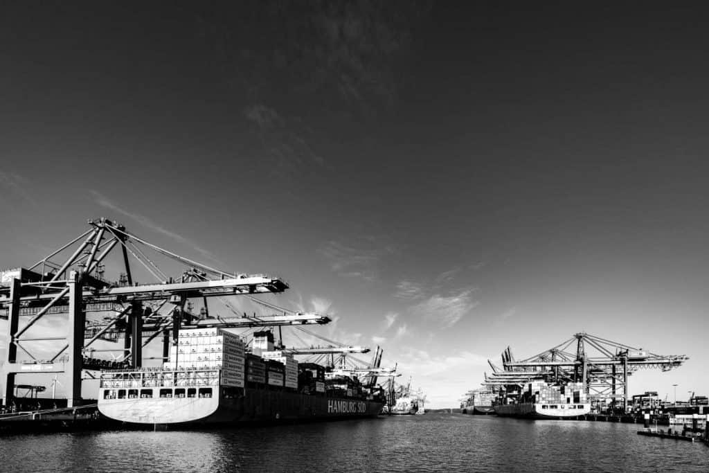 Blick in den Hamburger Hafen, links und rechts Containerschiffe mit Hafenkränen