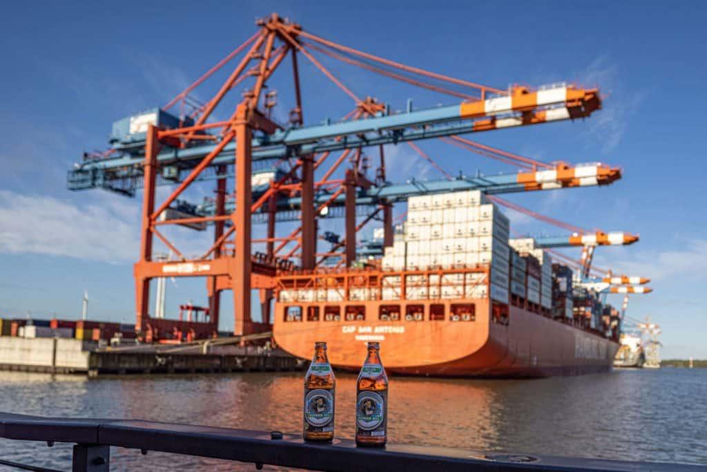 Zwei Bierflaschen auf einem Geländer, im Hintergrund Unscharf ein Containerschiff mit Hafenkränen