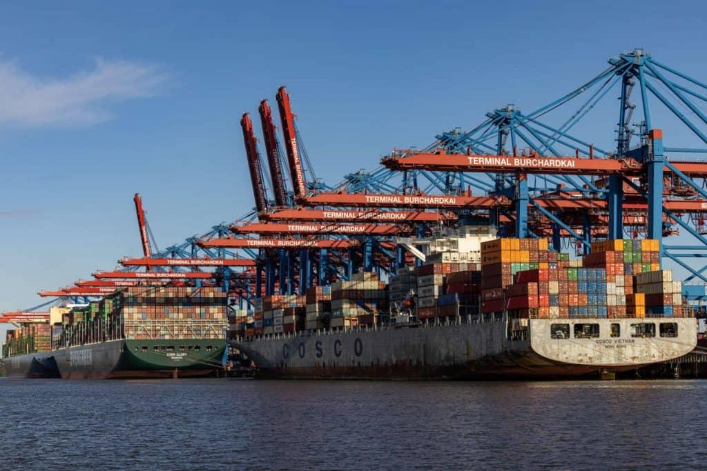 Drei Containerschiffe an der Kaimauer, Hafenkräne rechts daneben