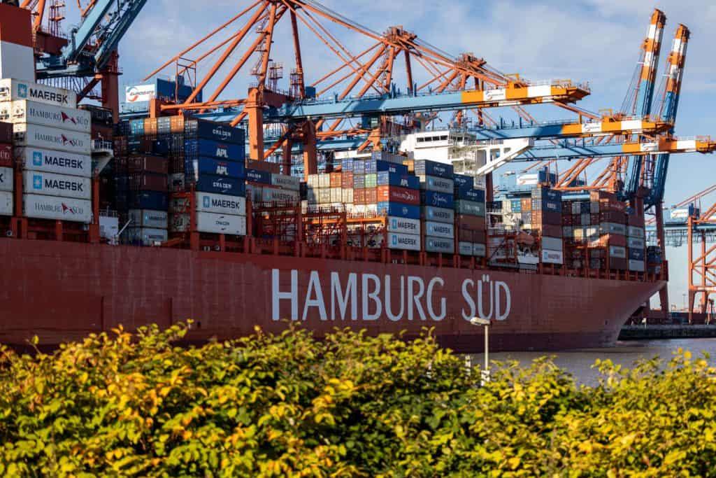 """Containerschiff mit der Aufschrift an der Bordwand """"Hamburg Süd"""", Hafenkräne und im Vordergrund einige Büsche"""