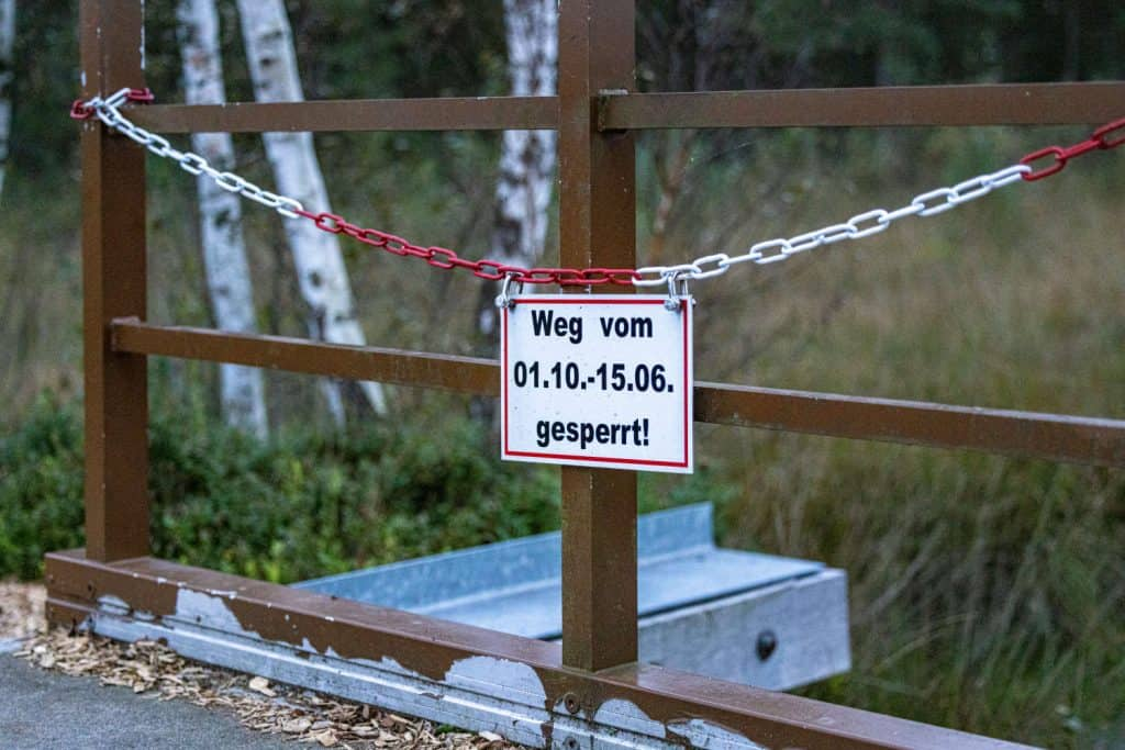 """Schild an einer rot-weißen Kette mit Aufschrift """"weg vom 01.10. - 15.06. gesperrt!"""""""