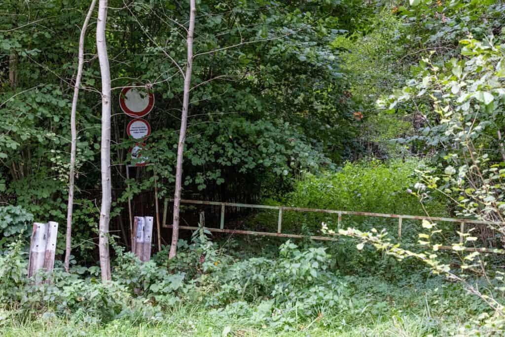 Ein verschlossenes Tor zugewachsen von diversen Pflanzen. Ein Straßenschild links am Bildrand